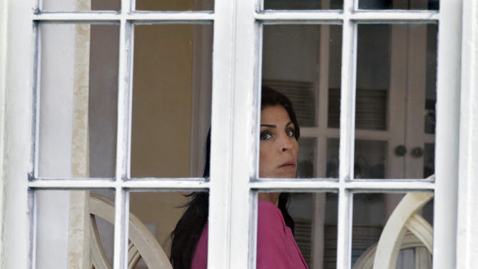 CORRECTS DATE - Jill Kelley looks out the window of her home Tuesday, Nov 13, 2012 in Tampa, Fla. Kelley is identified as the woman who allegedly received harassing emails from Gen. David Petraeus' paramour, Paula Broadwell. She serves as an unpaid social liaison to MacDill Air Force Base in Tampa, where the military's Central Command and Special Operations Command are located. (AP Photo/Chris O'Meara)