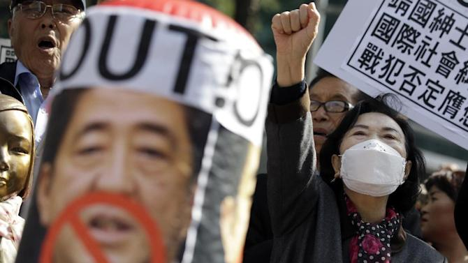 Protesters shout slogans during a rally against Japanese Prime Minister Shinzo Abe's policy about South Korean wartime sex slaves from the Japanese government in front of the Japanese Embassy in Seoul, South Korea, Wednesday, April 1, 2015. (AP Photo/Lee Jin-man)