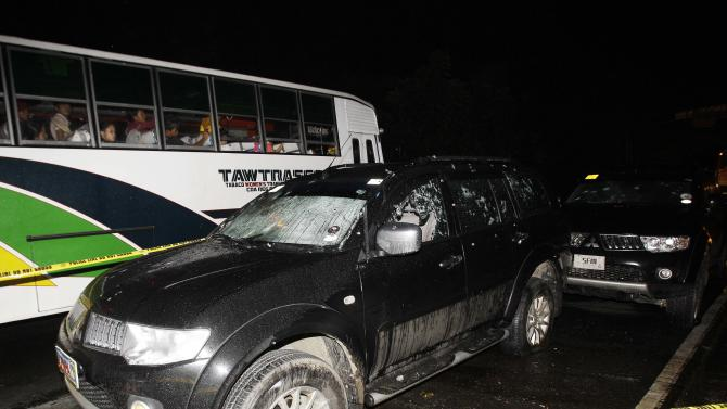 Passengers glance at the bullet-riddled vehicle of suspected criminals along a road in the town of Atimonan in Quezon province, about 140 kilometers (100 miles) southeast of Manila, Philippines late Sunday Jan. 6, 2013. Philippine army special forces and police killed 13 suspected criminals in a gunbattle Sunday in the latest violence to erupt in the country in the past week. (AP Photo/Aaron Favila)
