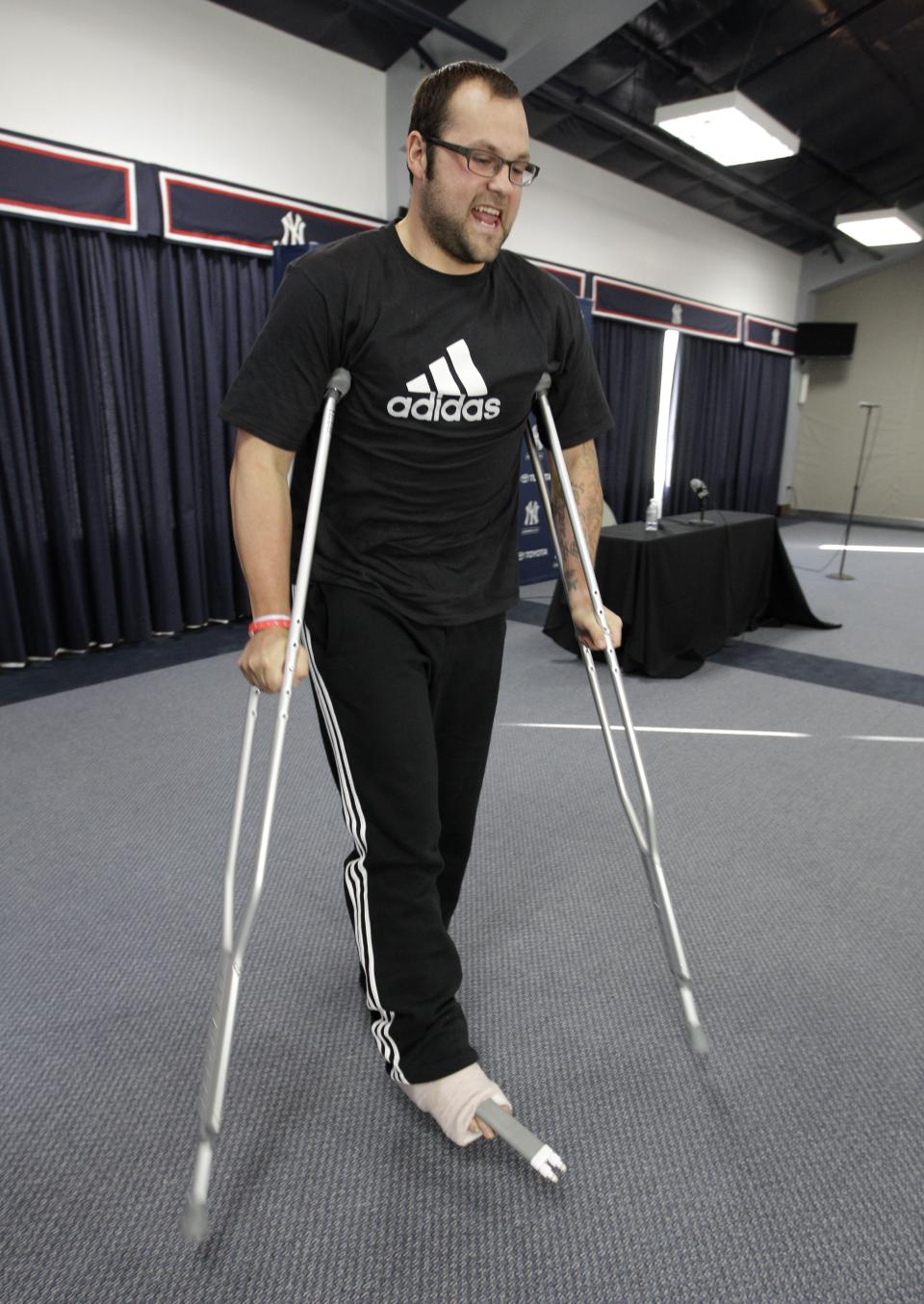 New York Yankees relief pitcher Joba Chamberlain uses crutches as he leaves a news conference during which he talked about his recent foot injury, at Steinbrenner Field in Tampa, Fla., Tuesday, March 27, 2012. Chamberlain injured his ankle jumping on a trampoline with his son while he was recovering from Tommy John surgery. (AP Photo/Kathy Willens)