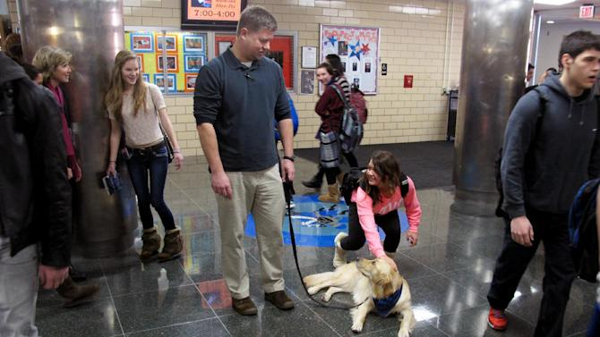 """In this Jan. 14, 2013 photo, Douglas Berg, a social worker at Prospect High School, watches as a student pets Junie, the school's """"therapy dog,"""" at the Mt. Prospect, Ill. school. Stress, anxiety and panic attacks are on the rise at many U.S. high schools, due to heightened academic expectations and troubles at home made worse by the shaky economy. So some schools are trying unconventional methods, such as therapy dogs, to help students cope. (AP Photo/Martha Irvine)"""