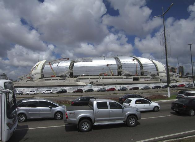 Cars drive past the outside of Arena Das Dunas stadium as work continues in preparation for the 2014 FIFA World Cup soccer championship in Natal, Brazil