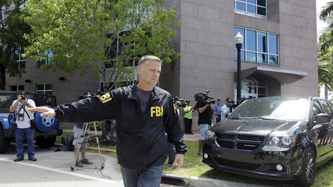 FBI agent guides a van after an operation inside the CONCACAF offices in Miami Beach, Florida