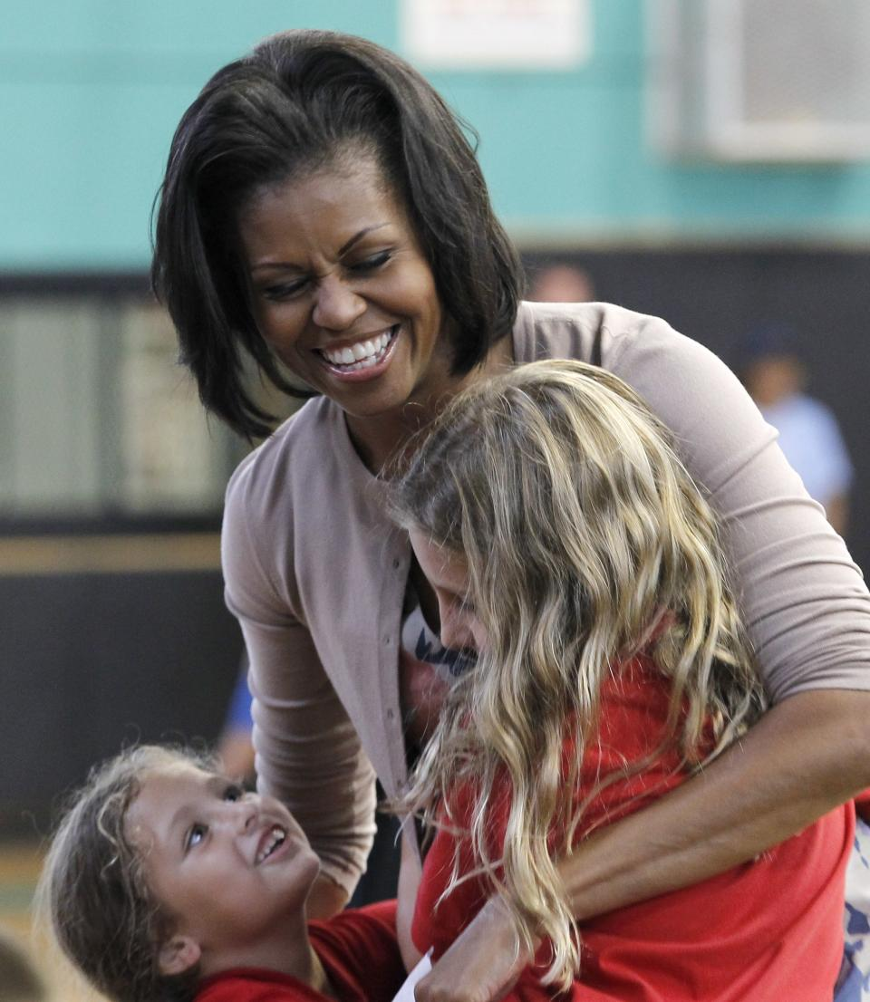 First Lady Michelle Obama laughs as she talks to two you children at the Holiday Park Gym, Wednesday, Aug. 22, 2012 in Fort Lauderdale, Fla. (AP Photo/Alan Diaz)