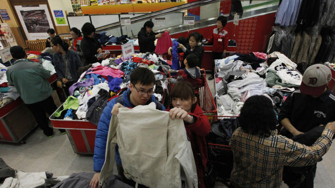 Customers choose clothes to buy at a discount store in Seoul, South Korea, Friday, April 5, 2013. Outsiders might hear the opening notes of a war in the deluge of threats and provocations from North Korea, but to South Koreans it is a familiar song. Foreigners unused to North Korean rumblings have canceled trips to the Korean Peninsula. But to get South Koreans' attention, Pyongyang must compete with the economy, celebrity scandals, baseball games and cherry blossoms. (AP Photo/Ahn Young-joon)
