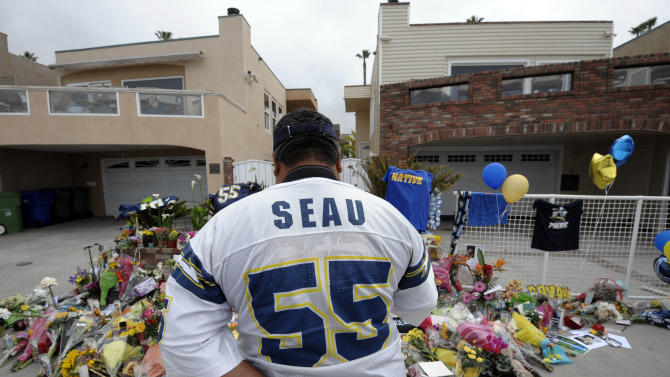 "San Diego Chargers fan Jerry Lopez looks over a memorial set-up in the driveway of the house of former NFL star Junior Seau Thursday, May 3, 2012, in Oceanside, Calif. Seau's apparent suicide stunned an entire city and saddened former teammates who recalled the former NFL star's ferocious tackles and habit of calling everybody around him ""Buddy.""  (AP Photo/Denis Poroy)"