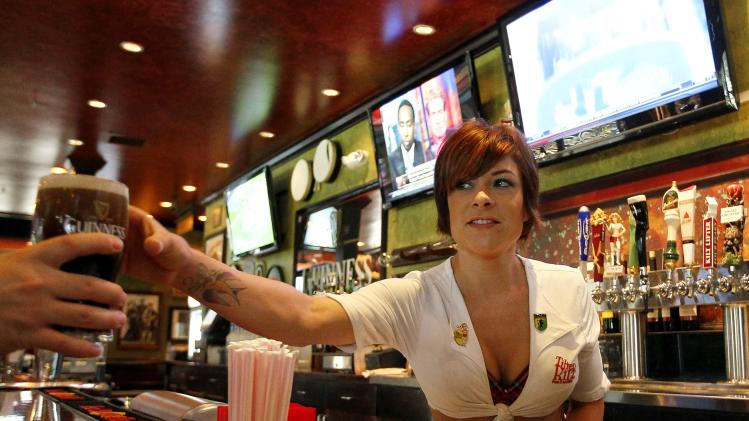 "In this May 16, 2012 photo, Carley Brusca serves a beer at the Tilted Kilt, in Tempe, Ariz. The Tilted Kilt is part of a booming niche in the beleaguered restaurant industry known as ""breastaurants,"" or sports bars that feature scantily-clad waitresses. These small chains operate in the tradition of Hooters, which pioneered the concept in the 1980s but has struggled in recent years to stay fresh. (AP Photo/Matt York)"