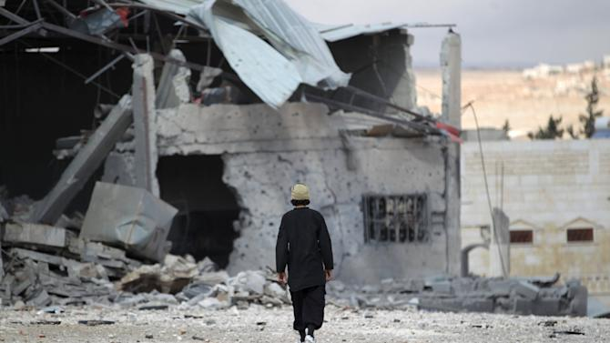 A man inspects a site hit by what activists said were airstrikes carried out by the Russian air force in the town of Babila
