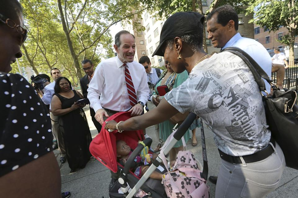 New York City comptroller candidate Eliot Spitzer, center, meets residents during a tour of the Frederick Douglass Houses, Wednesday, Aug. 21, 2013 in New York. Spitzer called for sweeping reforms to the public housing system and delivers a sharp rebuke of Mayor Michael Bloomberg's suggestion of fingerprinting tenants. (AP Photo/Mary Altaffer)
