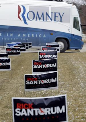 Campaign signs for Republican presidential candidate, former Pennsylvania Sen. Rick Santorum, cover the frozen ground as the campaign bus carrying Republican presidential candidate, former Massachusetts Gov. Mitt Romney, passes by en route to a campaign stop at the San Marino Club, Saturday, Feb. 25, 2012, in Troy, Mich.  (AP Photo/Eric Gay)