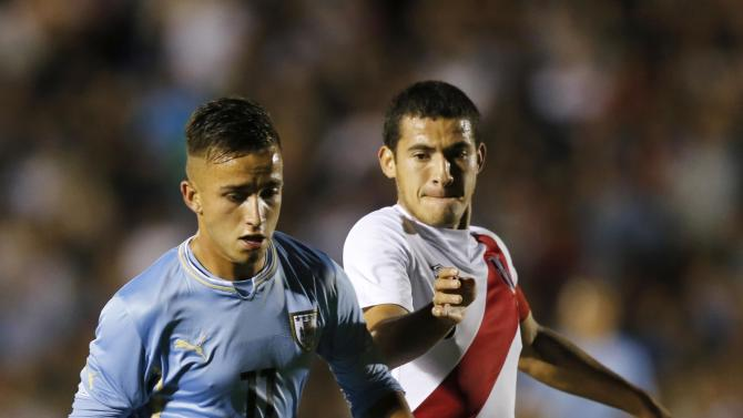 Uruguay's Franco Acosta and Peru's Brian Bernaola compete for the ball during their match for the final round of the South American Under-20 Championship in Montevideo