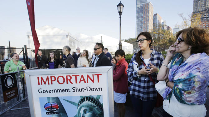 Tourists who had hoped to visit the Statue of Liberty stand near the dock used by Liberty Island ferries, Tuesday, Oct. 1, 2013 in New York. A government shutdown, the first since the winter of 1995-96, closed national parks across the nation. (AP Photo/Mark Lennihan)