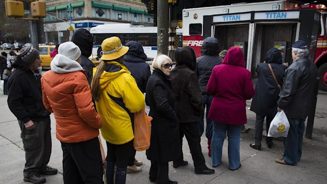 People wait to use a pay phone on Bright Beach Avenue, Wednesday, Oct. 31, 2012, in the Brooklyn borough of New York. People in the coastal corridor battered by superstorm Sandy took the first cautious steps Wednesday to reclaim routines upended by the disaster, even as rescuers combed neighborhoods strewn with debris and scarred by floods and fire. (AP Photo/ John Minchillo)