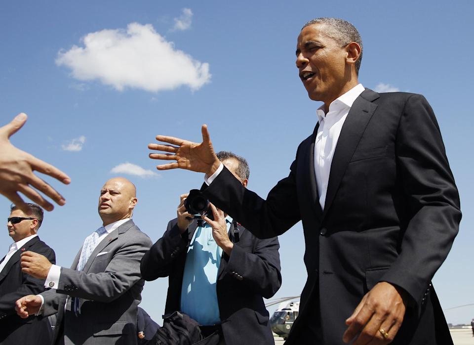 President Barack Obama greets people waiting for him on the tarmac as he arrives at O'Hare International Airport on Air Force One, Saturday, Aug. 11, 2012, in Chicago. (AP Photo/Carolyn Kaster)