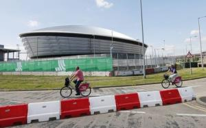People ride bicycles past the security perimeter of the SSE Hydro in Glasgow