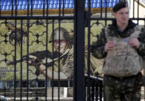 A Ukrainian soldier stands guard at the gate of a military…