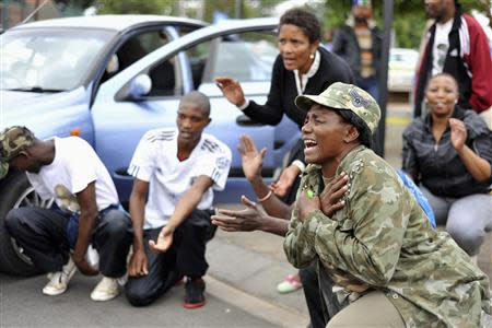 People react during gathering of mourners on Vilakazi Street in Soweto, where the former South African President Mandela resided when he lived in the township