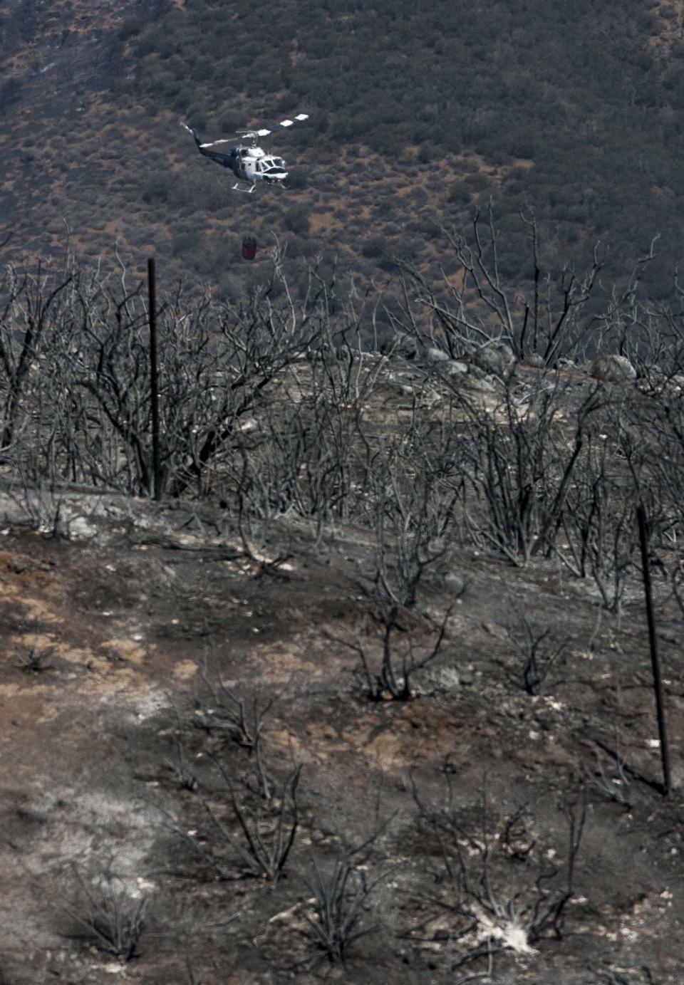 A helicopter positions itself for a drop on a hotspot near Point Mugu, Calif., Saturday, May 4, 2013. High winds and withering hot, dry air were replaced by the normal flow of damp air off the Pacific, significantly reducing fire activity. (AP Photo/Ringo H.W. Chiu)