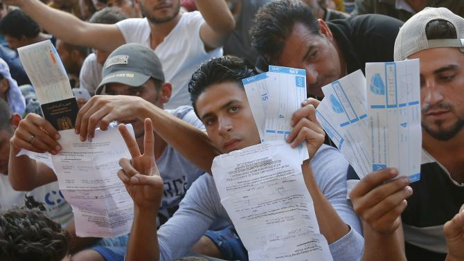 Refugees raise their documents and railways tickets outside the Keleti station in Budapest