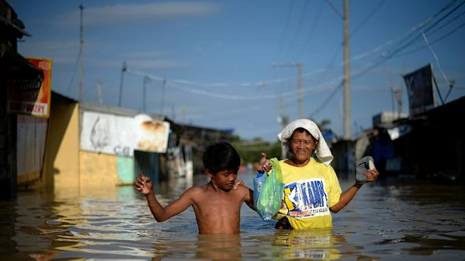 Residents wade through a flooded street in Calumpit, Bulacan province in the Philippines on October 22, 2015