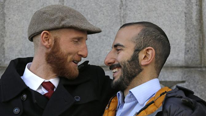 Derek Kitchen, left, and his partner Moudi Sbeity look at each other following court on Wednesday, Dec. 4, 2013, in Salt Lake City. A challenge to Utah's same-sex marriage ban by three gay couples was back in court Wednesday as a federal court judge heard arguments in a case. Kitchen and Sbeity are plaintiff's in this case. (AP Photo/Rick Bowmer)