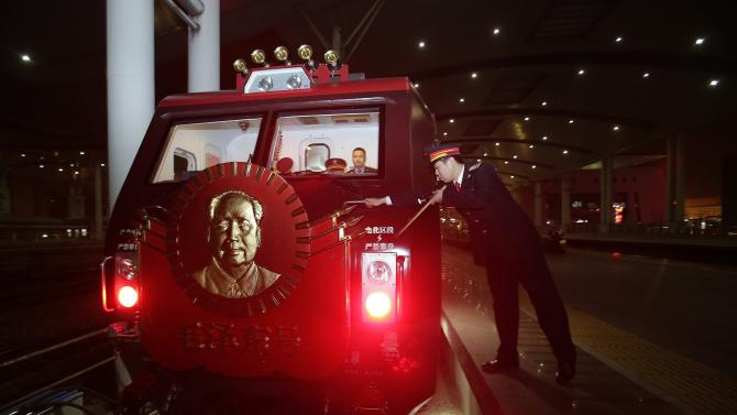 "A train driver checks the ""Mao Zedong"" locomotive as it makes a stop at a railway station in Wuhan"