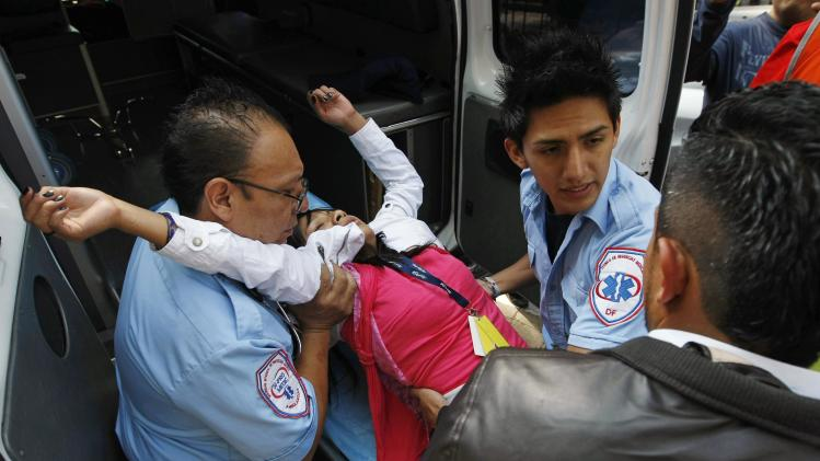 Paramedics assist a woman who fainted after she and co-workers were evacuated following an earthquake in Mexico City