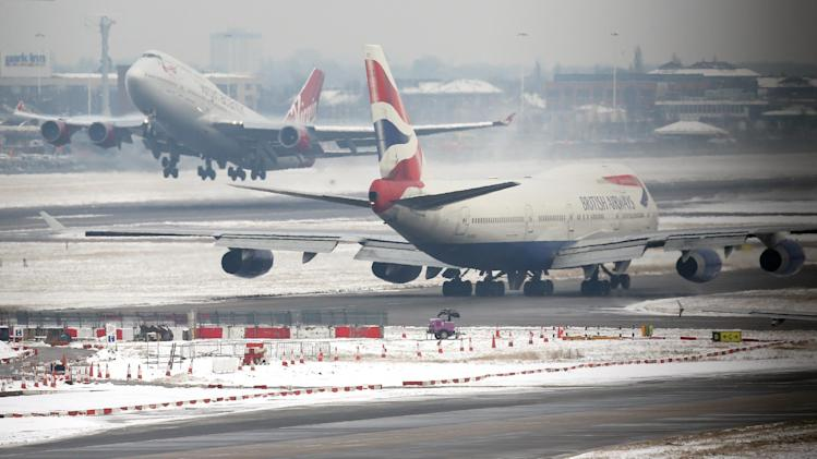 Planes take off and taxi at Heathrow Airport in London as the winter weather continued affect flights on Monday January 21, 2013. Heathrow planned to cancel 10 percent of its flights  on Monday . (AP Photo/Steve Parsons/PA ) UNITED KINGDOM OUT