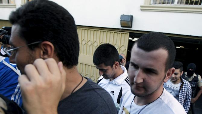 A policeman escorts four of five Syrian men from a court room after they were freed from jail in Tegucigalpa