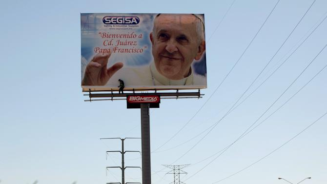 Worker checks a billboard promoting the upcoming visit of Pope Francis in Ciudad Juarez