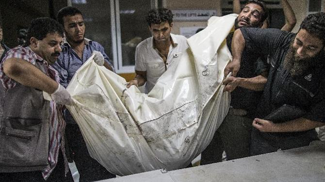 Palestinian volunteers at Gaza City's al-Shifa hospital load a body bag with the remains of children on a stretcher, on July 21, 2014, after an Israeli air strike in Gaza City