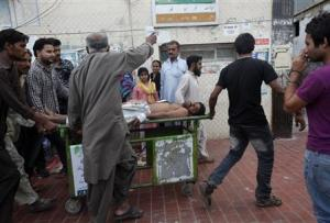 Rescue workers and relatives wheel an injured man on a stretcher, who was attacked by unknown gunmen, in Karachi