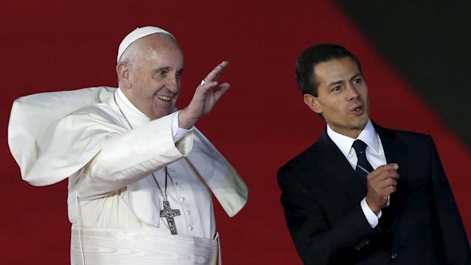 Pope Francis waves while walking with Mexico's President Pena Nieto after his arrival in Mexico City