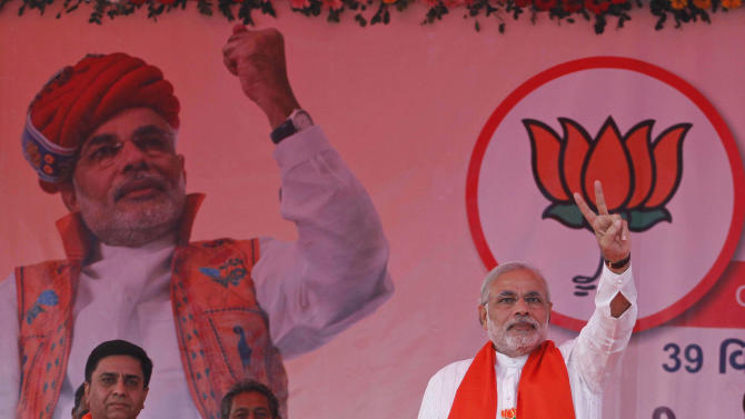 In this Monday, Dec. 3, 2012 photo, Gujarat Chief Minister Narendra Modi, right, flashes a victory sign during an election campaign at Viramgam, Gujarat, India. Eleven years after Modi became the chief minister of the western state of Gujarat - and 10 years after brutal anti-Muslim rioting left over a 1,100 people there dead - Modi is campaigning for his third term. Nearly everyone expects him to be swept into office, and the top leadership of his rightwing Bharatiya Janata Party is already hailing him as a future prime minister. But few politicians in India are as polarizing as Modi. (AP Photo/Ajit Solanki)