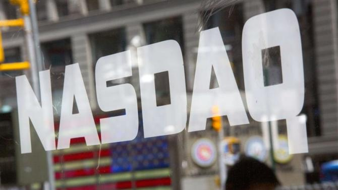 File of a man walking past the Nasdaq MarketSite in New York's Times Square