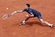 Serbia's Novak Djokovic hits a return to Spain's Rafael Nadal during their Men's Singles final tennis match of the French Open tennis tournament at the Roland Garros stadium, on June 11, 2012 in Paris.     AFP PHOTO / KENZO TRIBOUILLARDKENZO TRIBOUILLARD/AFP/GettyImages