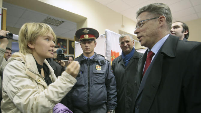 Opposition activist Yevgenia Chirikova, left, speaks to Khimki acting mayor Oleg Shakhov at a polling station in the town of Khimki, outside Moscow, Russia, Sunday, Oct. 14, 2012. Chirikova who played a major role in the massive winter protests against Putin's rule, is challenging the incumbent mayor. She has complained of an uneven playing field, saying authorities tried to thwart her meetings with voters and put up other obstacles. (AP Photo/Mikhail Metzel)