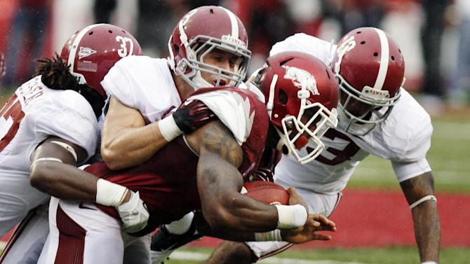 Arkansas running back Knile Davis pushes through Alabama defensive backs Robert Lester (37), Vinnie Sunseri (3) and Deion Belue, right, during the second quarter of an NCAA college football game in Fayetteville, Ark., Saturday, Sept. 15, 2012. (AP Photo/Danny Johnston)