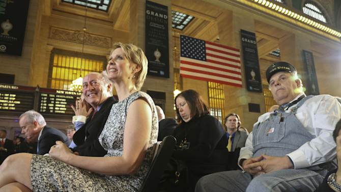 New York poet Billy Collins, second from left, Broadway star Cynthia Nixon, third from left, and retired Amtrak conductor Tom Savio, right, are among invited guests attending the Grand Central Terminal centennial celebration on Friday, Feb. 1, 2013 in New York. Grand Central, once in danger of being demolished, is celebrating its 100th birthday with speeches, a brass band and a rollback to 1913 prices when a slice of cheesecake might go for 19 cents. The majestic Beaux Arts building, known as Grand Central station although it is technically a terminal, is one of the world's most popular tourist destinations.   (AP Photo/Bebeto Matthews)
