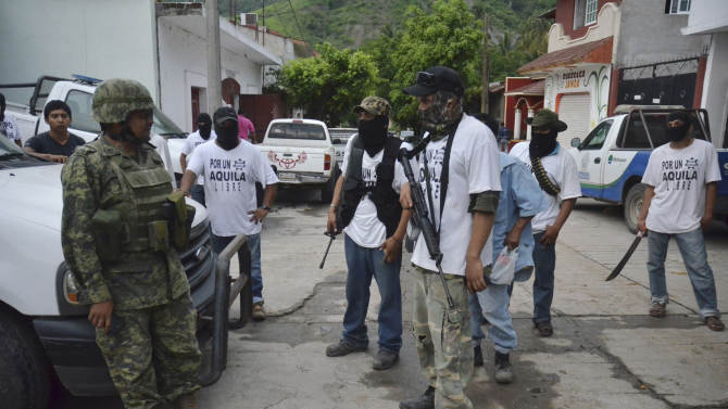 "**CORRECTS DAY TO WEDNESDAY** A Mexican army soldier talks to armed members of a local self-defense group wearing white T-shirts with the slogan ""For a Free Aquila"" in the town of Aquila, Mexico, early Wednesday, July 24, 2013. Mexico's rough western state of Michoacan, where Aquila is located, is proving just as tough a thorn in the side of President Enrique Pena Nieto as it was for his predecessor after gunmen believed to be working for the Knights Templar cartel launched a coordinated series of a half-dozen ambushes on federal police convoys last Tuesday followed by yet another self-defense group that has sprung up to fight against the Knights Templar.(AP Photo/Gustavo Aguado)"