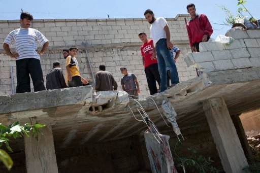 "Residents of Kfar Sijna look at the roof of a house, allegedly damaged after a tank shell was fired by Syrian government forces based in nearby Khan Sheikhun, in the north of Idlib province, on July 10. The major powers started talks Thursday on a UN Security Council resolution on Syria with Russia declaring a ""red line"" against sanctions"