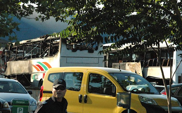 Bulgarian policeman is seen in front of destroyed buses at Burgas Airport, outside the Black Sea city of Burgas, Bulgaria, some 400 kilometers (250 miles) east of the capital, Sofia, Wednesday, July 18, 2012. A bus carrying young Israeli tourists in a Bulgarian resort exploded Wednesday, at least killing three people and wounding at least 20, police said. Witnesses told Israeli media that the huge blast occurred soon after someone boarded the vehicle. (AP Photo/ Bulphoto Agency) BULGARIA OUT