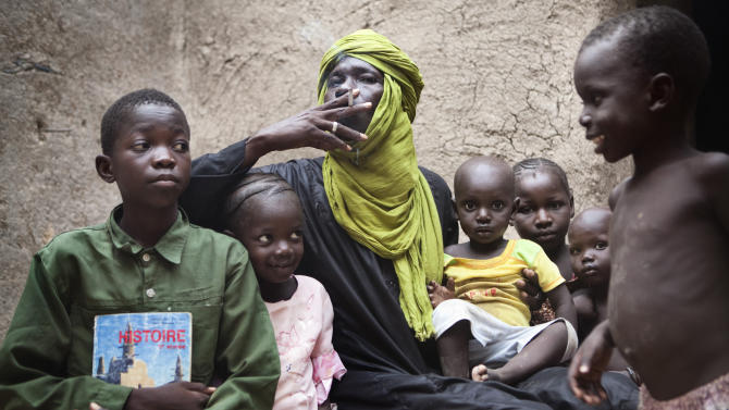 In this Thursday, Sept. 27, 2012 photo, former Timbuktu souvenir vendor Mamadou Sekere smokes alongside some of his children at the home where they have taken refuge in Mopti, Mali. Before Islamists seized the northern half of Mali, Sekere sold masks and jewelry in Timbuktu to European tourists who rode camels and slept in the desert under the stars. Ordinary Malians and international experts alike are not sure what will reunite and bring back political stability to a country that until recently had a reputation as one of West Africa's most steady democracies. Representatives of the United Nations, the African Union and regional body ECOWAS are to consider the situation on Oct. 19, 2012 in a meeting in Mali's capital, Bamako. (AP Photo)