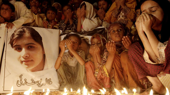 "Pakistani children pray for the recovery of 14-year-old schoolgirl Malala Yousufzai, who was shot on Tuesday by the Taliban for speaking out in support of education for women, during a candlelight vigil in Karachi, Pakistan, Friday, Oct. 12, 2012. A Pakistani military spokesman says Yousufzai is in ""satisfactory"" condition but cautions that the next few days will be critical. Writing reads on the poster left, ""Malala Yousufzai.""(AP Photo/Shakil Adil)"