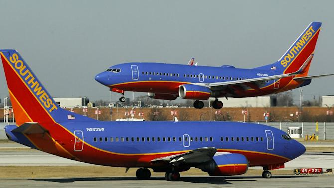 """FILE - In this Feb. 9, 2012, file photo, a Southwest Airlines Boeing 737 waits to take off at Chicago's Midway Airport as another lands. The government can require airlines to show consumers a total ticket price that includes taxes and fees in print and online ads, the U.S. Court of Appeals said Tuesday, July 24, 2012, rejecting an industry challenge to a series of consumer protection regulations. The Department of Transportation, which issued the regulations last year, has the authority to regulate """"unfair and deceptive"""" airline industry practices, the three-member panel said in its ruling. The ruling also covers two other regulations: A requirement that airlines allow consumers who purchase tickets more than a week in advance the option of canceling their reservations without penalty within 24 hours after purchase, and a ban on airlines increasing the price of tickets or baggage fees after tickets have been bought. The rules had been challenged by Spirit and Southwest airlines, with the support of two major airline industry trade associations. (AP Photo/Charles Rex Arbogast, File)"""