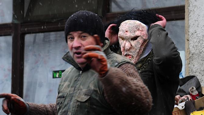 In this picture taken Saturday, Jan. 12, 2013, villagers prepare masks of cannibals, made from natural materials, a day before the carnival in Macedonia's southwestern village of Vevcani.  The masks are a tightly kept secret until the day when hundreds of villagers parade on the streets. Said to date from pagan times 1,400 years ago, the Vevcani carnival, with its colorful floats and masked revelers, has grown in popularity over the last decade and attracts thousands of visitors for the celebrations on St. Vasilij Day to welcome in the New Year, according to the Julian calendar. (AP Photo/Boris Grdanoski)