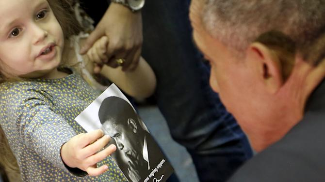 A girl shows U.S. President Obama a picture of himself as he visits her classroom after his remarks on Jewish American History Month at the Adas Israel Congregation synagogue in Washington