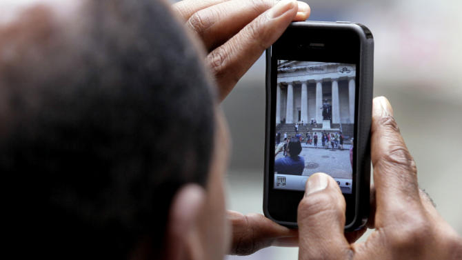 FILE- In this Wednesday, May 30, 2012, file photo, a tourist uses his iPhone to photograph Federal Hall in New York's Financial District, Wednesday, May 30, 2012. Leap Wireless International Inc., the parent of the Cricket cellphone service, on Thursday, May 31, 2012, said it will be the first mainland U.S. phone company to sell the iPhone on a prepaid, no-contract basis.  (AP Photo/Richard Drew)