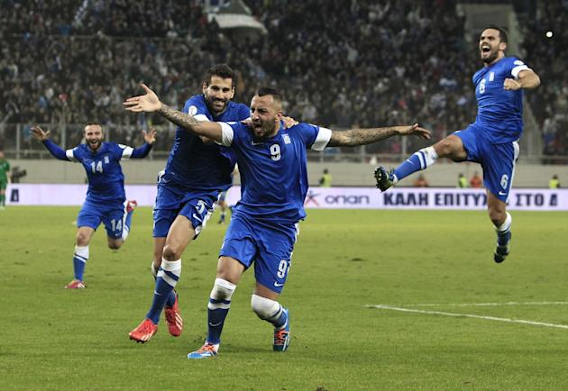 Greece's Kostas Mitroglou, center, celebrates after scoring the third goal of his team against Romania during their World Cup qualifying playoff first leg soccer match at the Karaiskaki stadium in the