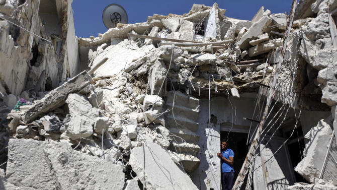 A Syrian man looks out of the rubble as rescuers, not shown, look for the bodies of two girls thought to be under the rubble of a building hit by a Syrian government airstrike in Aleppo, Syria, Sunday, Aug. 19, 2012 (AP Photo/ Khalil Hamra)